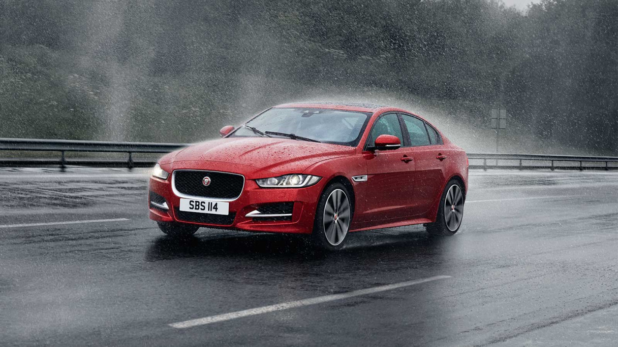 Jaguar XE in red driving on a road in heavy rain.