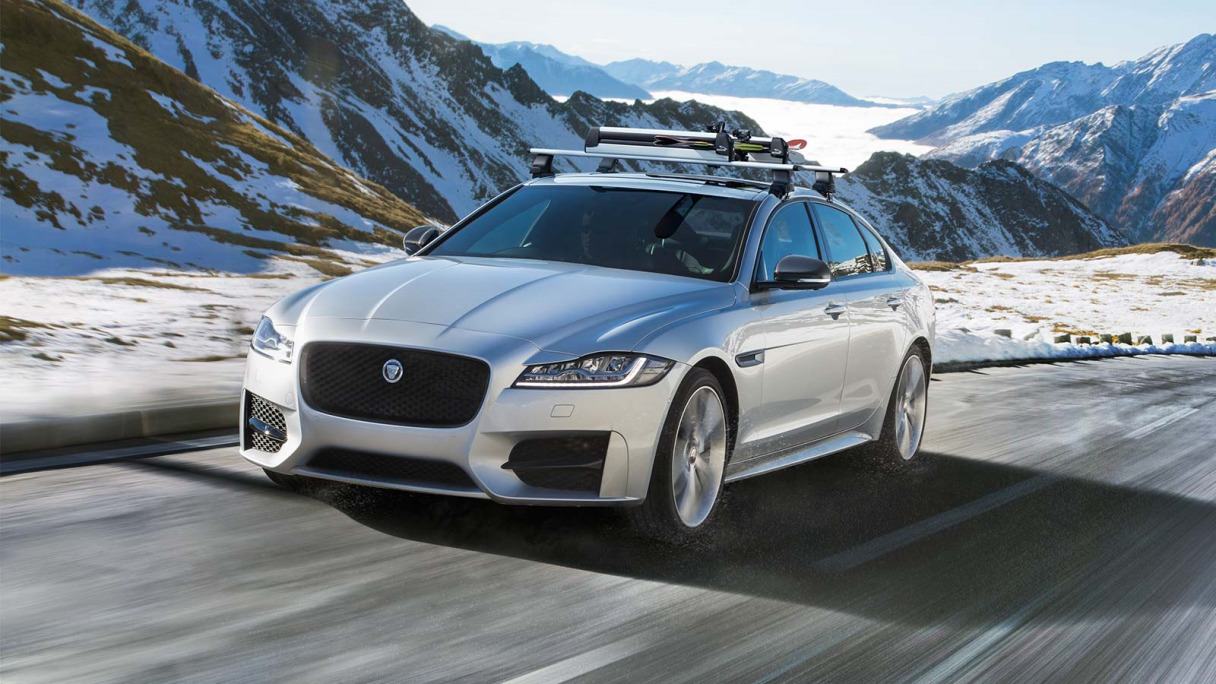 Jaguar XF in silver driving on a road in a snowy landscape