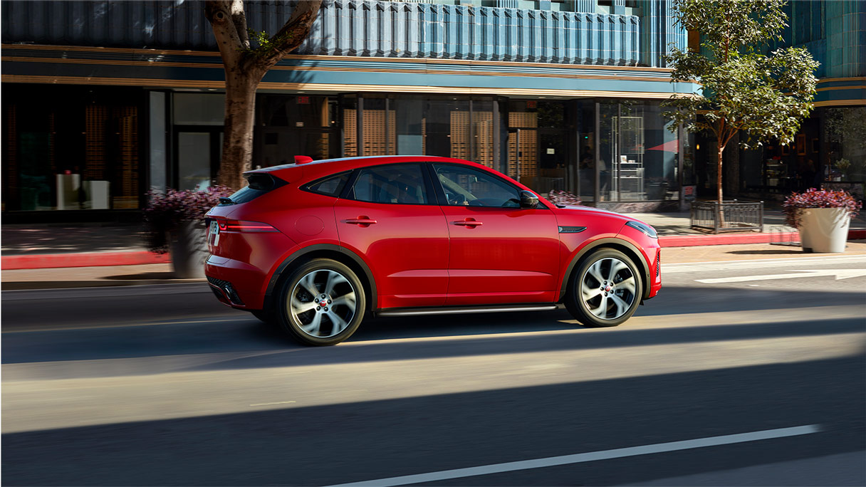 Red Jaguar E-Pace driving through city.