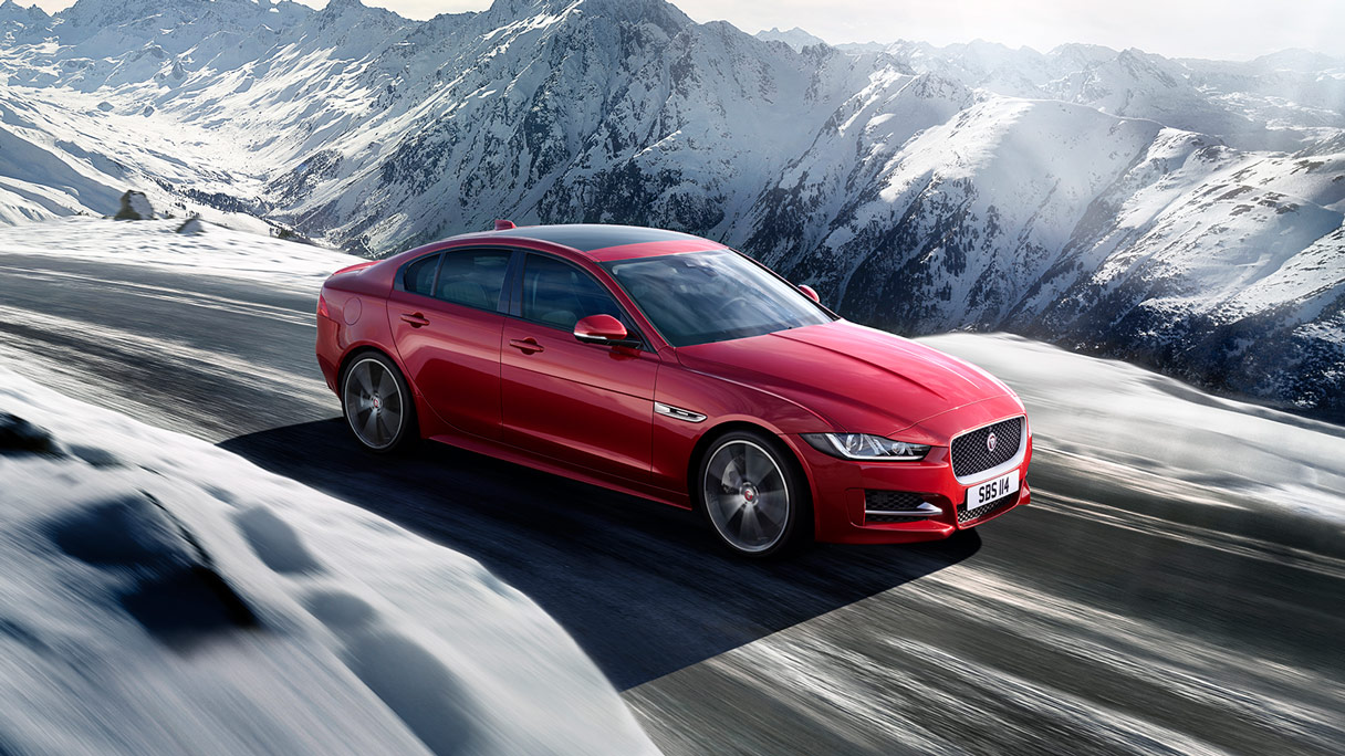 Red Jaguar XE driving on winter road.