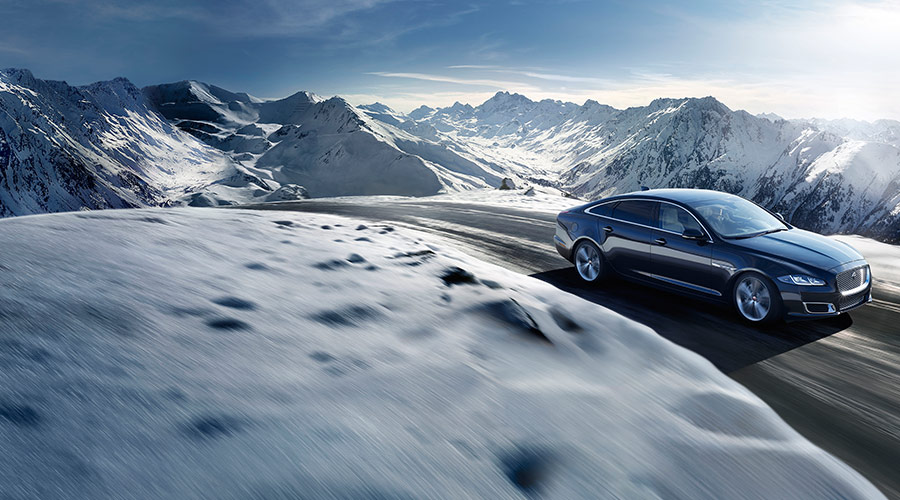 Jaguar XJ driving along a snowy mountain road.