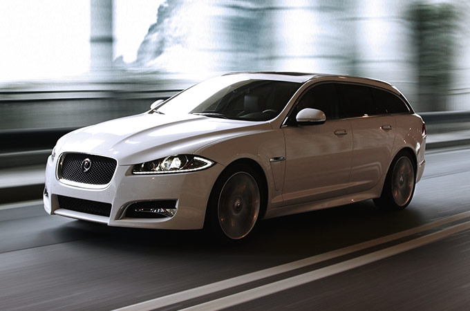 White Jaguar XF Sportbrake driving on road.