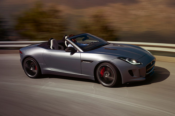 Grey Jaguar F-Type Convertible driving on road.