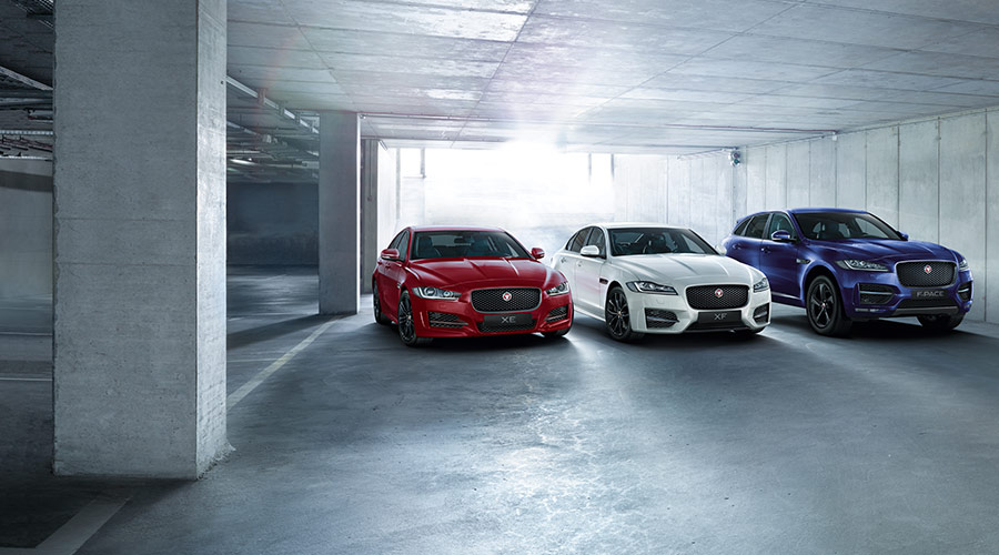 A red XE, white XF and blue F-PACE parked in a garage.