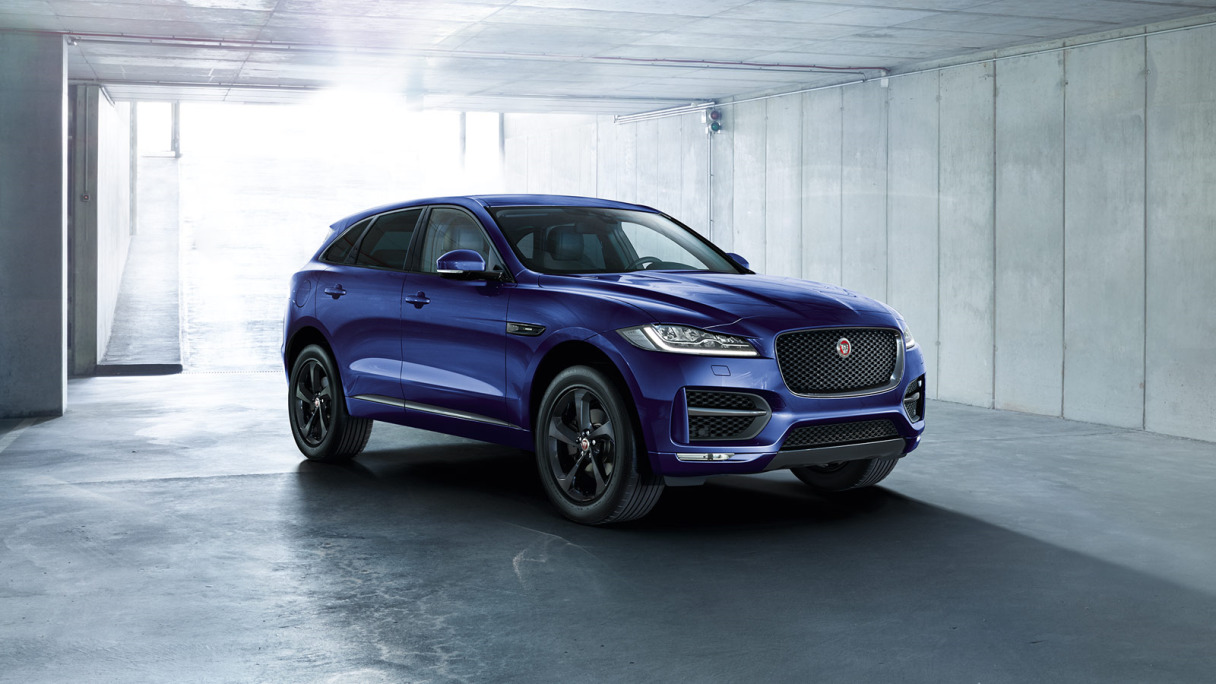 A blue Jaguar F-Pace parked in a garage.