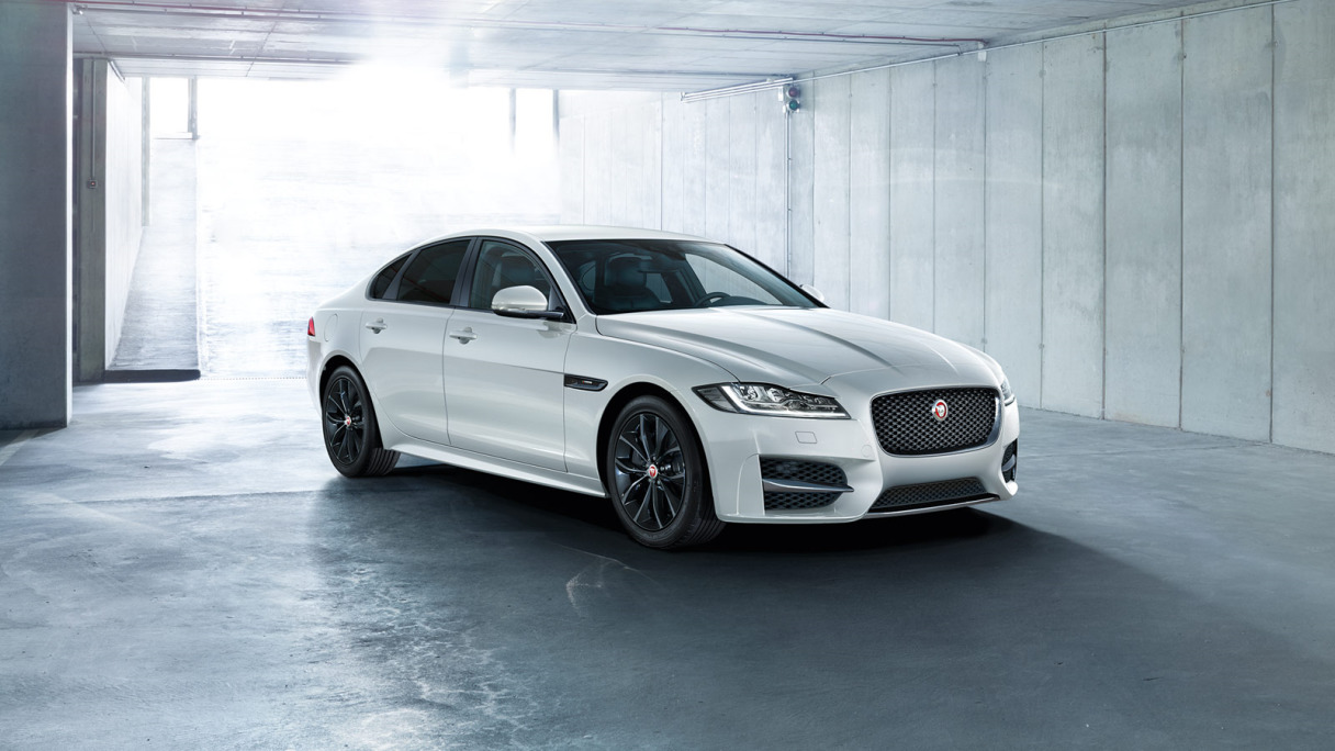 A white Jaguar XF parked in a garage.
