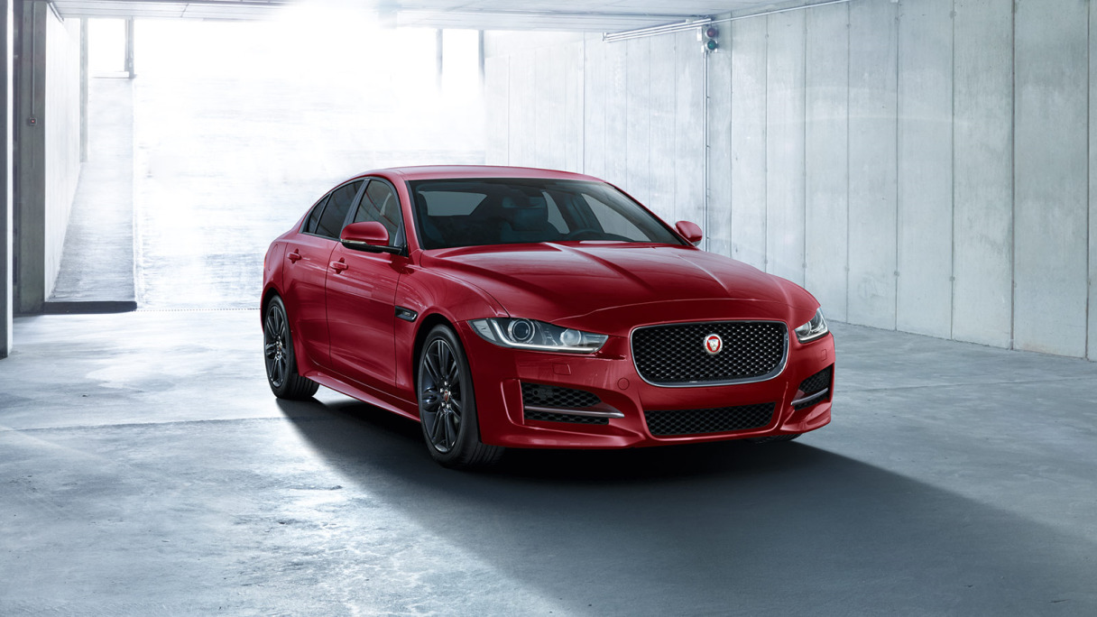 A red Jaguar XE parked in a garage.