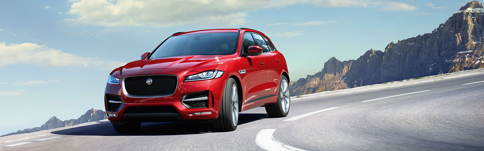 Red F-Pace on road in front of mountain range