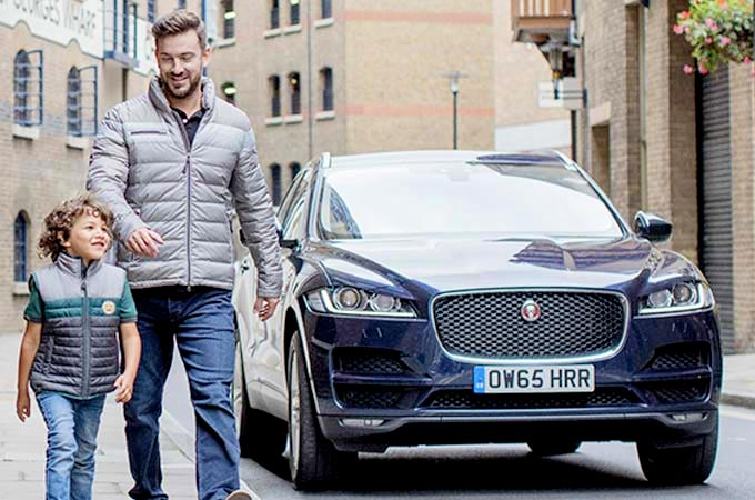 A man and child walking away from their f-pace wearing jaguar apparel.