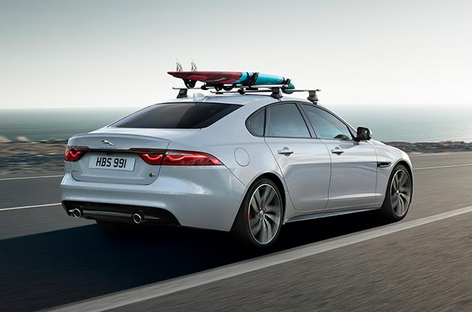Jaguar driving down a road with the roof carrying accessory, carrying a surfboard.