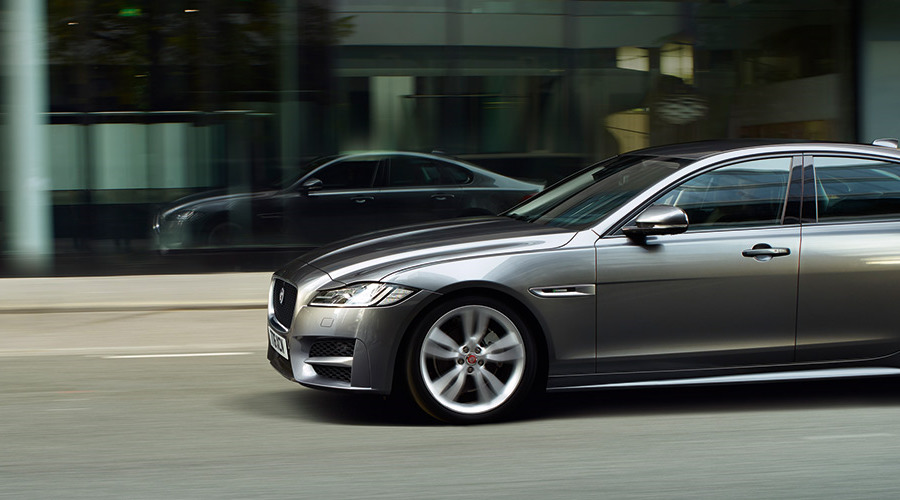Silver Jaguar XF driving on-road, in the city