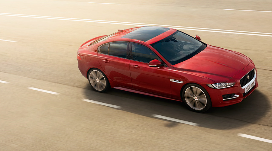 Red Jaguar XE driving on-road