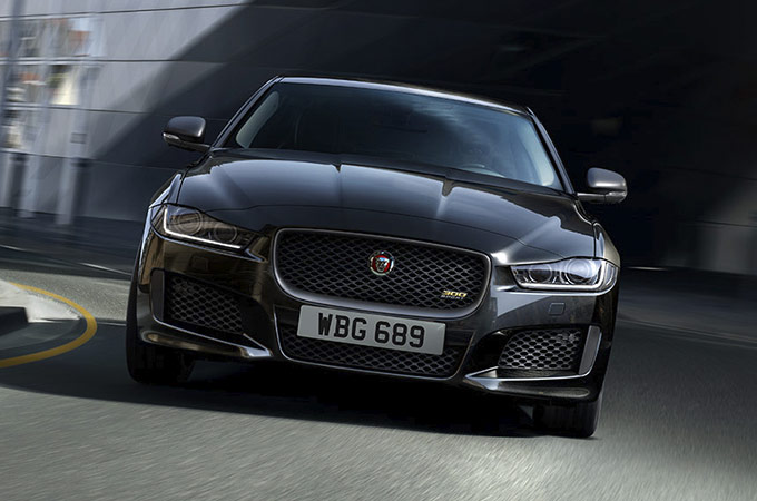 The front of a jaguar Xe 300 sport driving on a road.