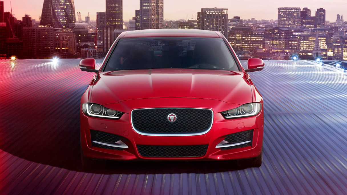 Red Jaguar XE Front View With a City Backdrop