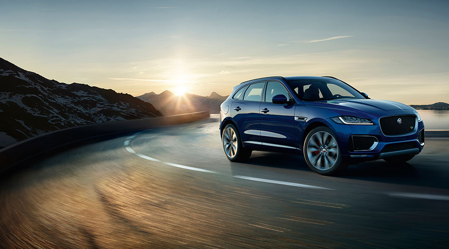 F-PACE driving on road at sunset.