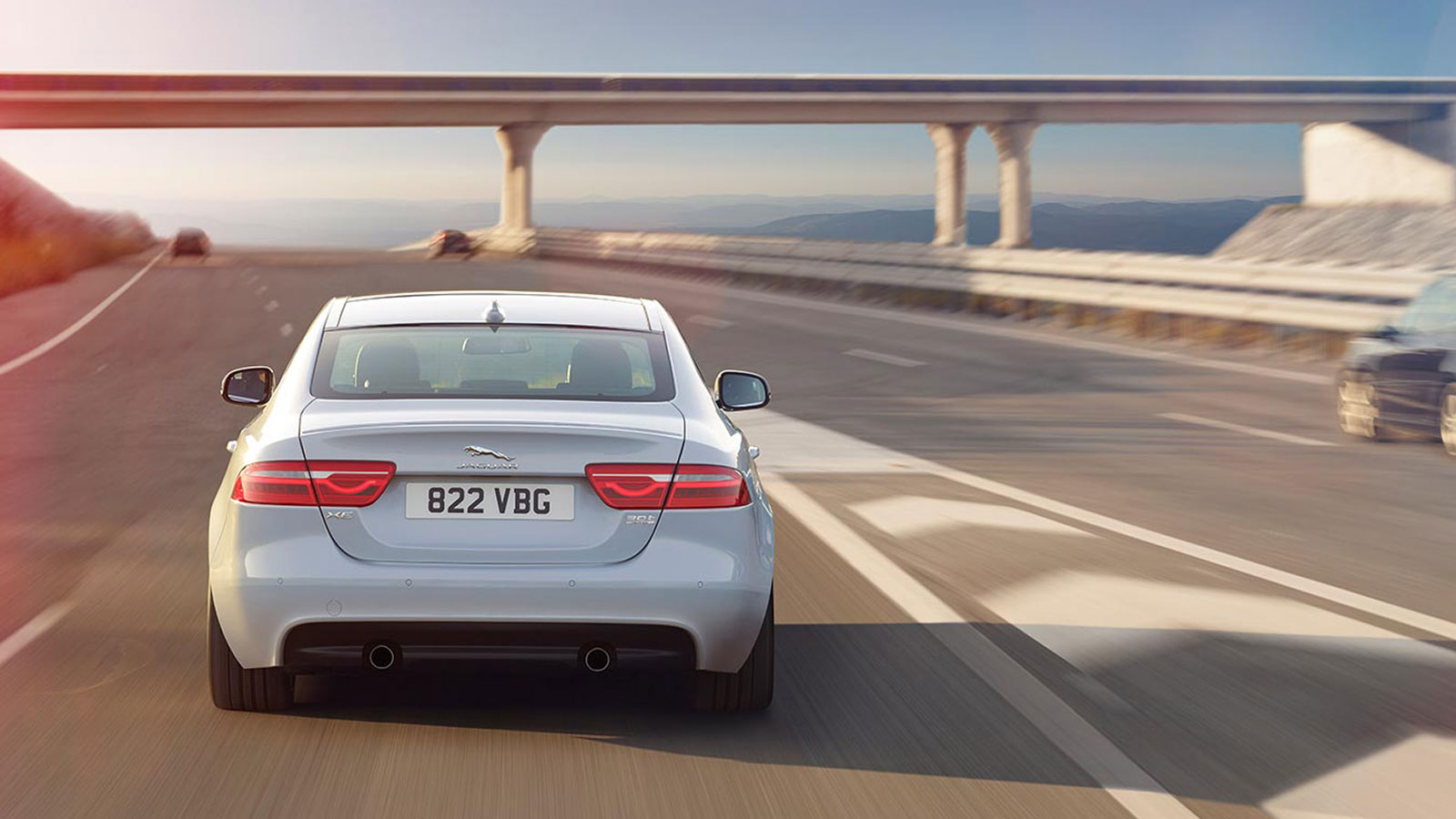 Rear view of Jaguar XE S, driving on a freeway.