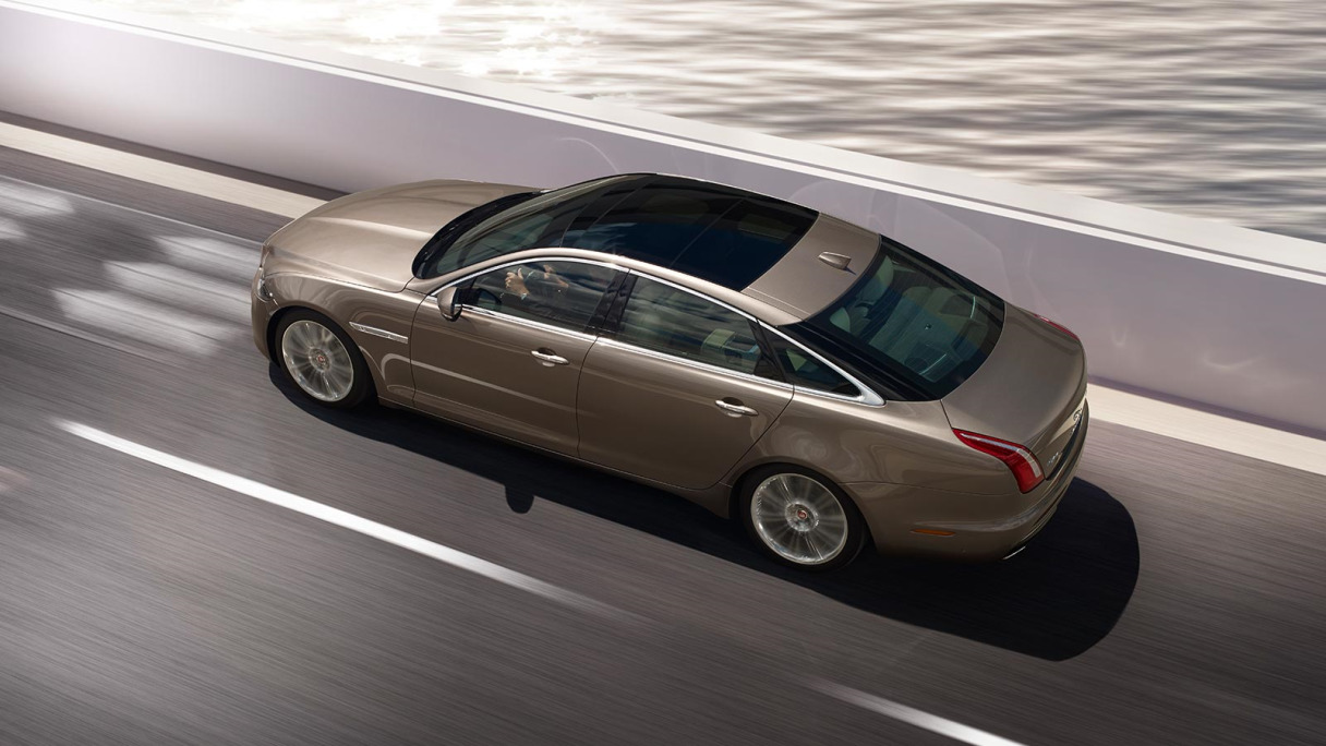 Above view of Jaguar driving on road next to the sea.