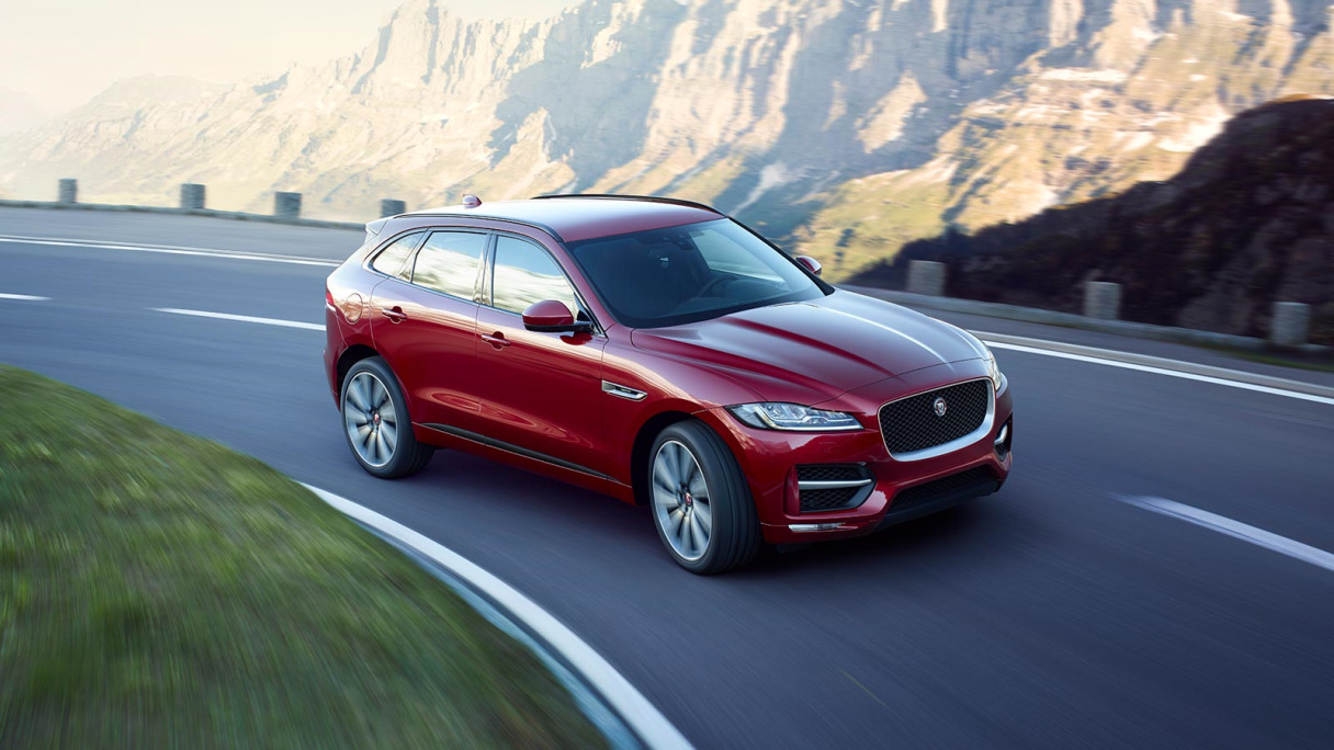 Red Jaguar F-PACE driving on mountain road.