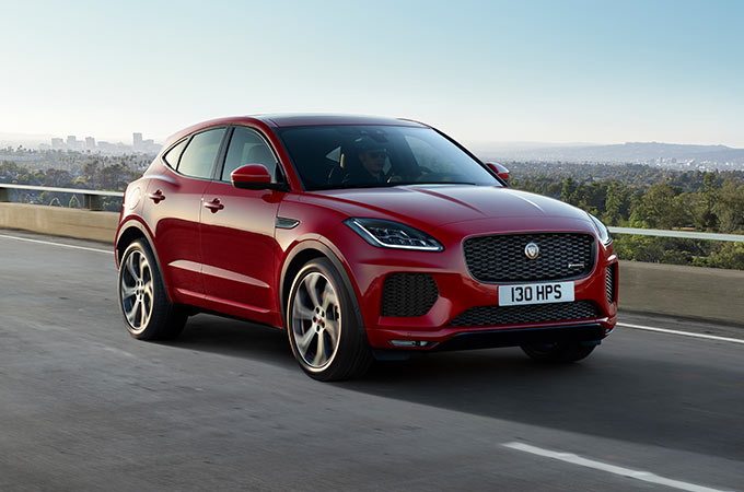 Red Jaguar E-PACE driving on the road.