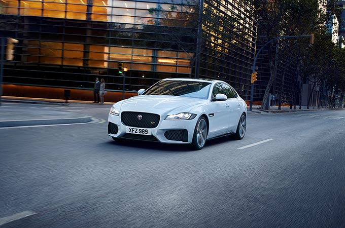 White Jaguar XF driving in the city.