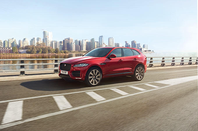 Red Jaguar E-PACE driving with a city backdrop.