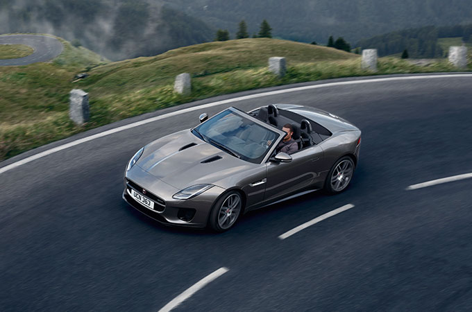 Grey Jaguar F-TYPE Convertible drives on a winding road in the mountains.