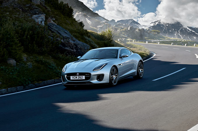 Silver Jaguar F-TYPE Coupe driving with a mountainous backdrop.