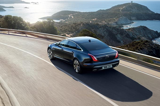 Blue Jaguar XJ driving on-road, near the sea.