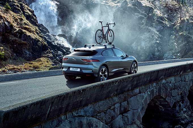 Jaguar I-PACE with a mounted bike drives over a bridge.