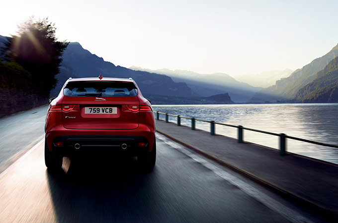 Red Jaguar E-PACE drives alongside a lake.
