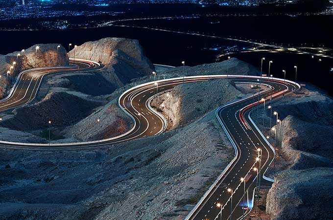 Long exposure shot of a winding road lit up at night.