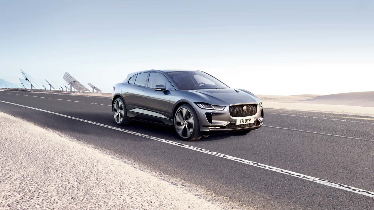 Jaguar I-PACE driving on-road next to a sandy landscape.