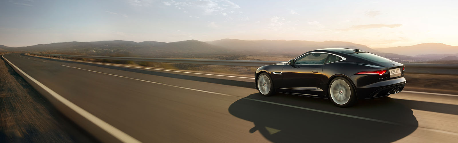 Side view of black F-TYPE driving.