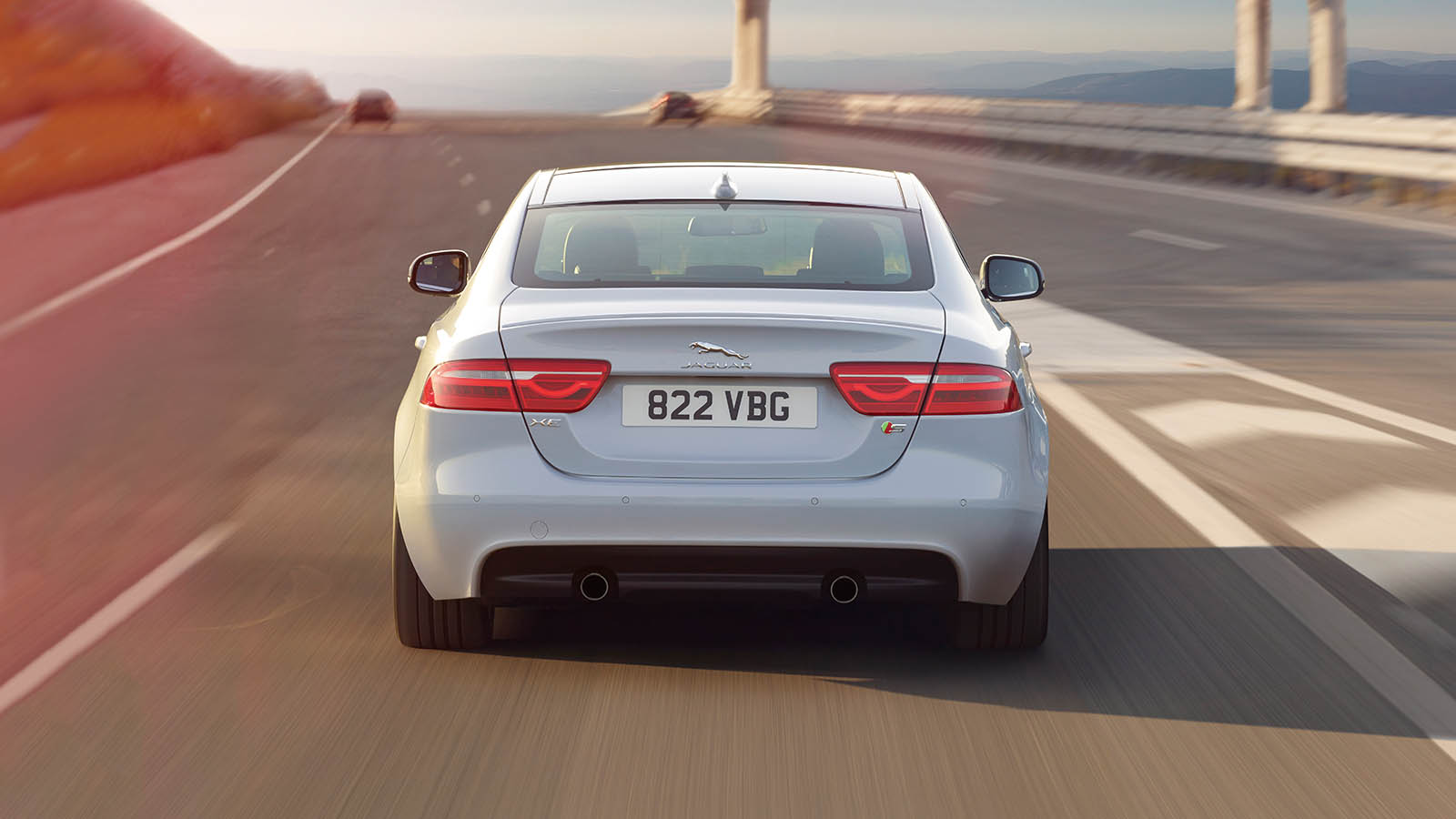 A White Jaguar XE Driving On A Highway.
