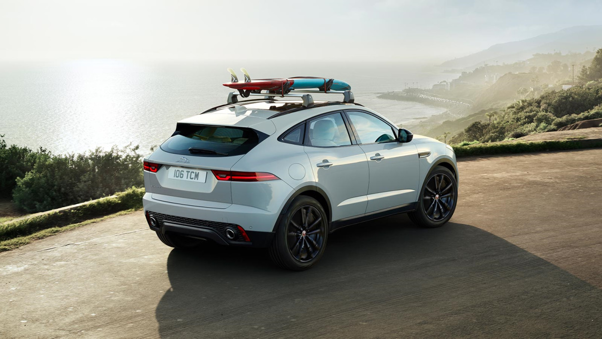 Jaguar driving on a panoramic view road, with surfboard attached.