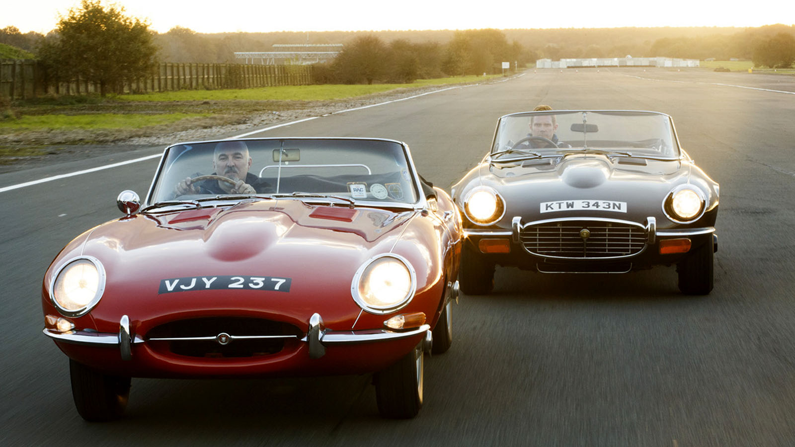 Two Classic Jaguars Driving On A Track With Headlights On.