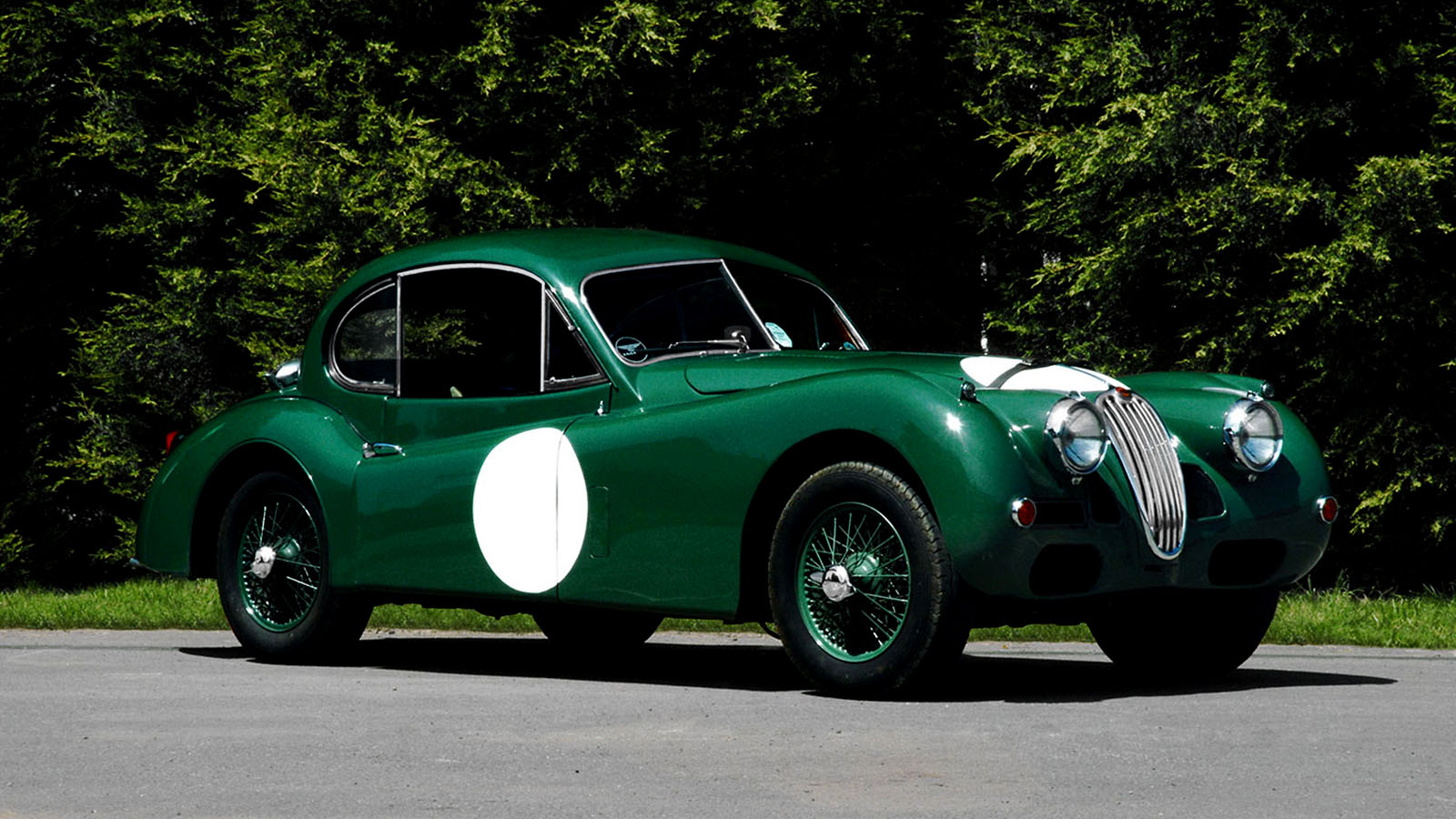 Classic Green Jaguar Parked By Some Trees.