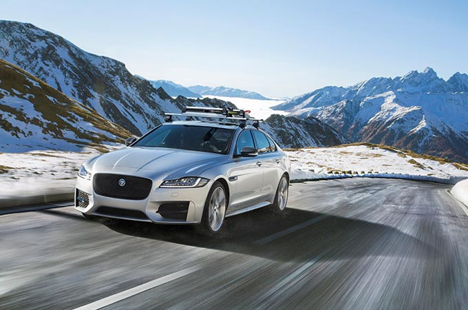 Silver car with snow covered mountains behind