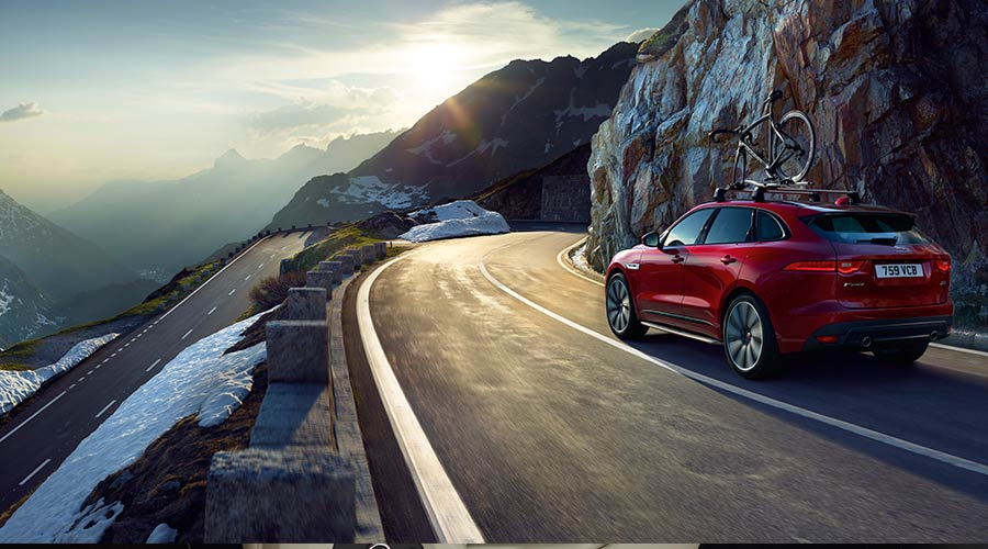 A Red Jaguar Driving On A Mountain Road.