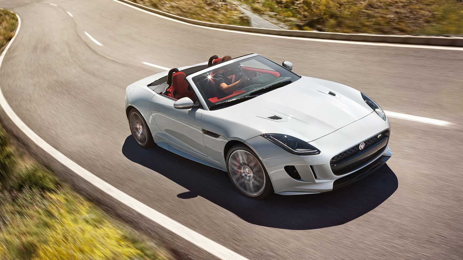 A White Jaguar Convertible Driving On A Road.
