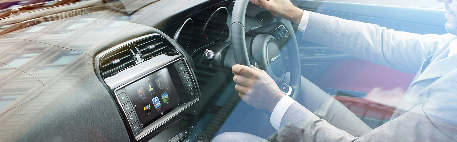 Interior view of Man driving a Jaguar.