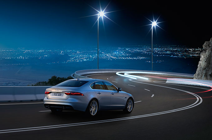 A Silver Jaguar Driving At Night.