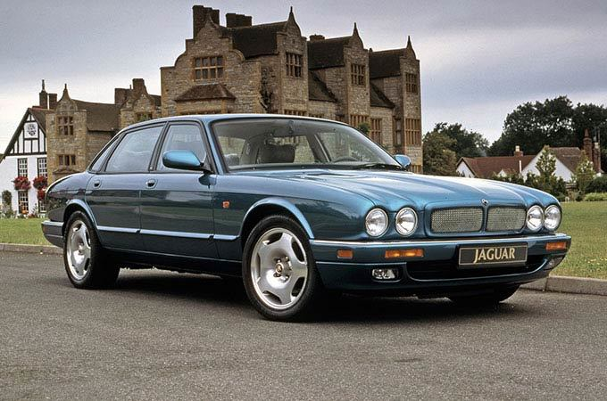 A Blue 1994 Jaguar XJR X300 In Front Of An Old House.