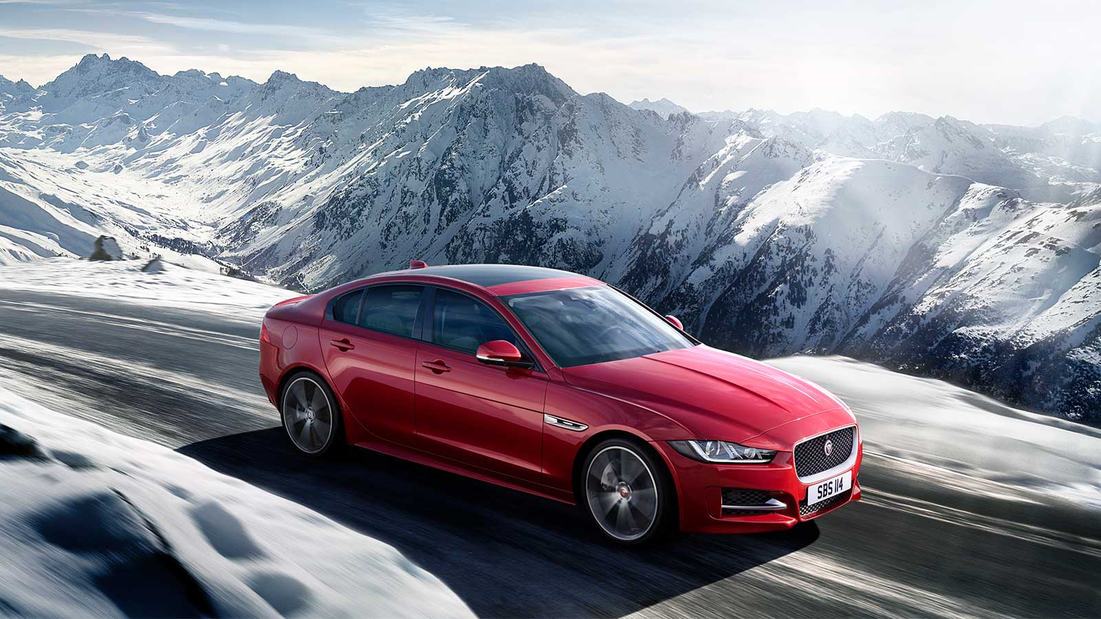 A Red Jaguar Driving Through Some Mountains.