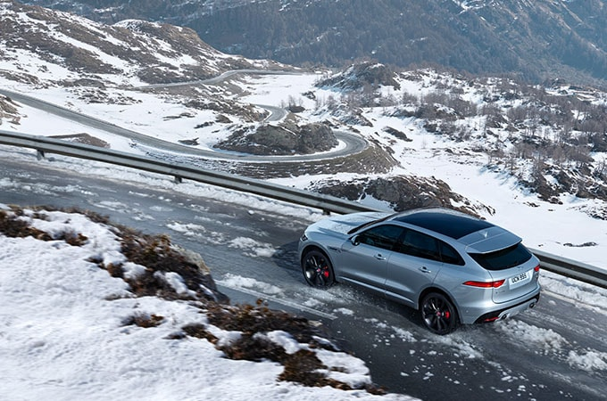 Grey Jaguar driving on snowy mountain road
