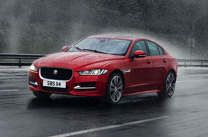 Red Jaguar driving in rain
