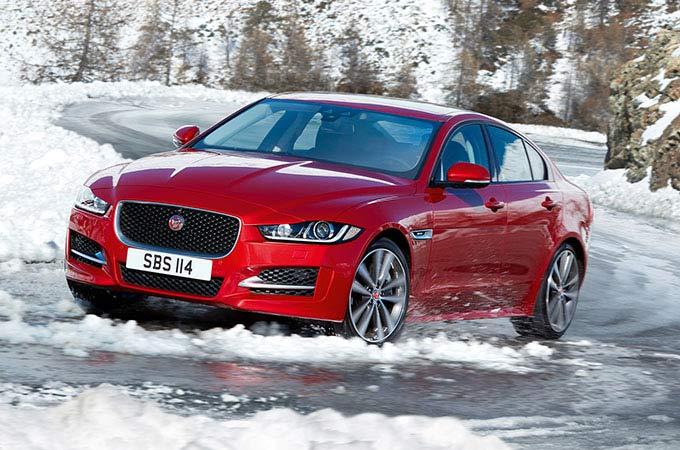 Red Jaguar XE on snowy road.