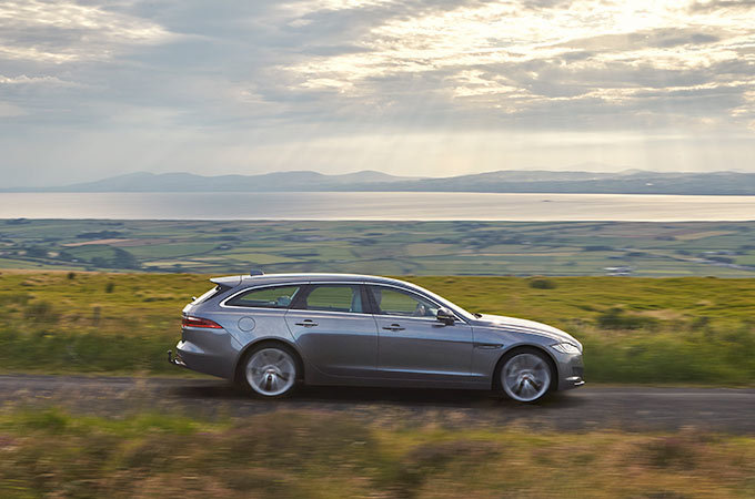 Side view of Jaguar XF Sportbrake, driving along a country road, with the sea in the background