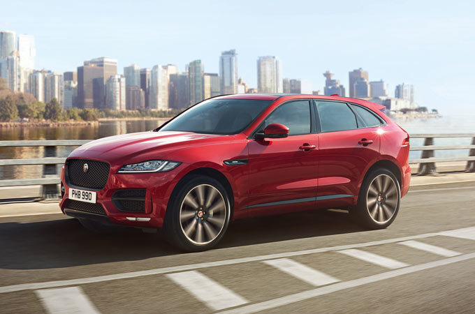 Jaguar F-PACE in red drives across a bridge, with a city in the background
