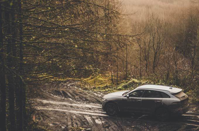 Mud-covered Jaguar F-PACE drives through a forest